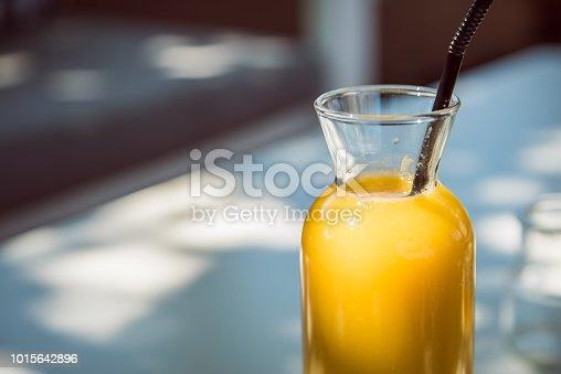 Orange juice in a glass bottle with a black straw