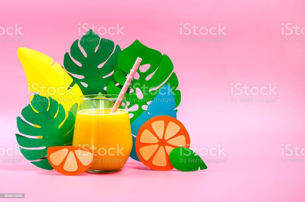 Orange juice in a grass with paper leaves and orange on side. stock photo