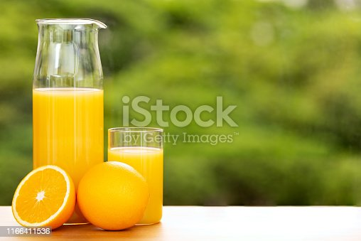 Orange juice in a jug and a glass with full and cut orange by a window opening to green tree tops, shallow depth of field. large copy space.