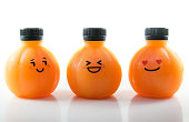Orange juice in a plastic spherical bottle with emotional face. Isolated on white background