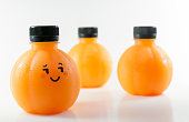 Orange juice in a plastic spherical bottles with emotional face. Isolated on white background