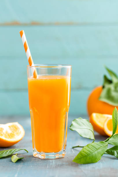 Orange juice in glass and fresh fruits with leaves on wooden background, vitamin drink or cocktail stock photo