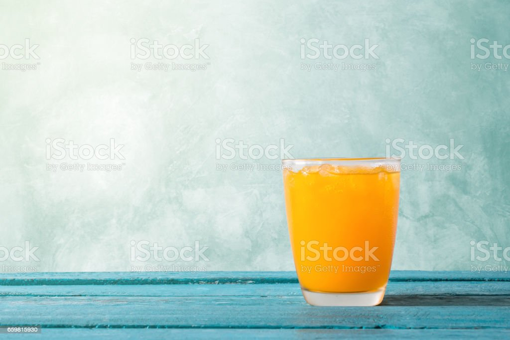Orange juice in glass with ice on ocean blue wooden summer time concept. stock photo