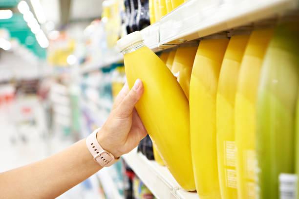 Orange juice in hands buyer in shop stock photo