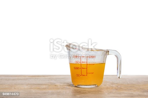 Orange juice in measuring cup isolated on white background
