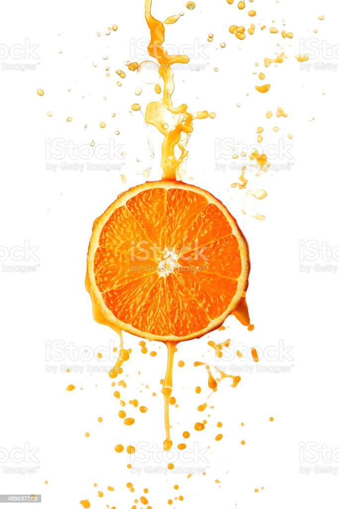 Orange juice splashing against white background stock photo