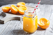 Orange Juice Squeezed In glass jar with fund rustic