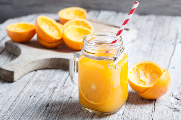 Orange Juice Squeezed In glass jar with fund rustic stock photo