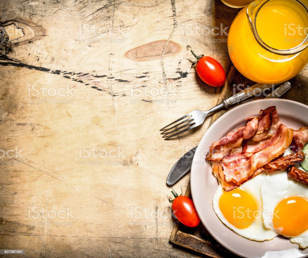 Orange juice with fried eggs, bacon, and slices of bread. stock photo