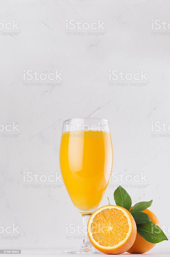 Orange juice with half cut oranges and green leaves on white wooden...