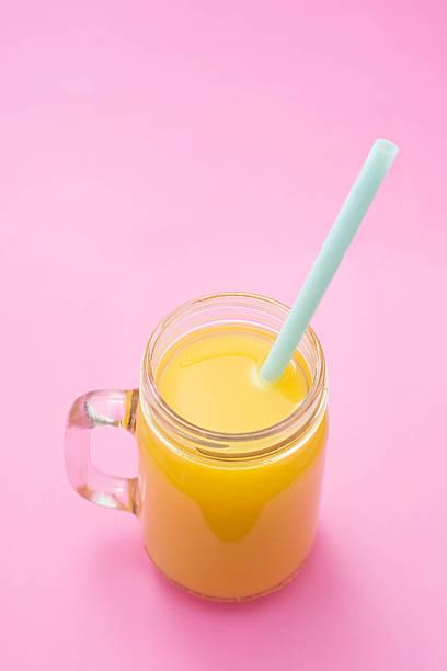 orangensaft mit stroh, im einmachglas, isoliert auf rosa hintergrund. nahaufnahme, raum, ansicht von oben kopieren. - pop up stock-fotos und bilder