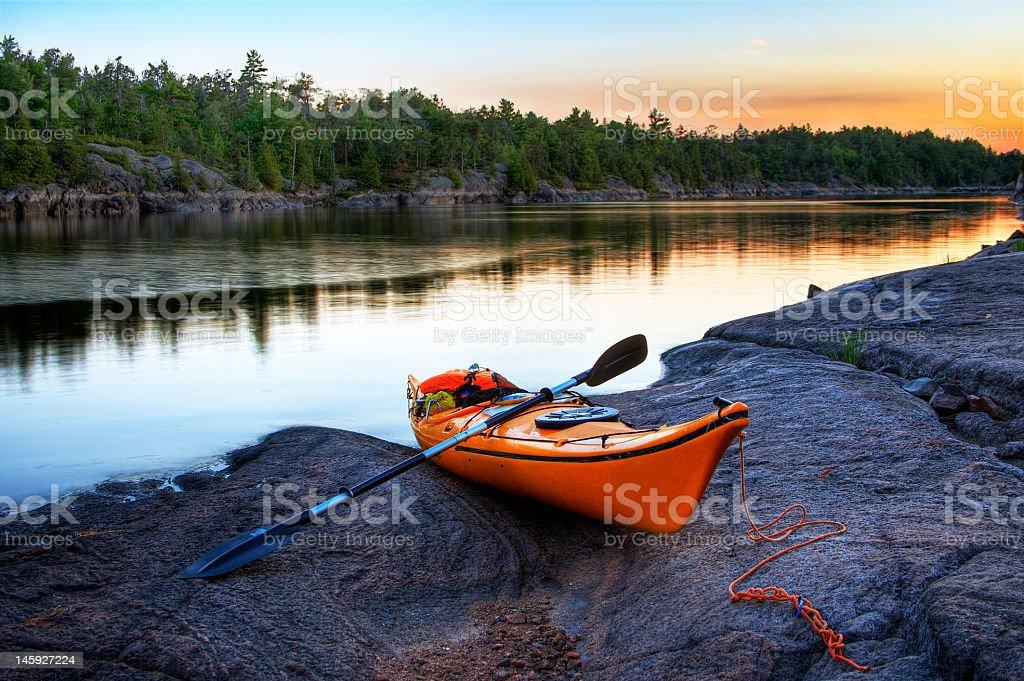 Orange kayak berthing at the shore of a lake stock photo