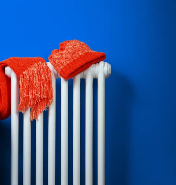 Orange stricken, Mütze und Schal auf weißen Heizkörper am blauen Wand Hintergrund liegend – Foto