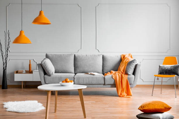 Orange lamp above grey scandinavian sofa in modern interior