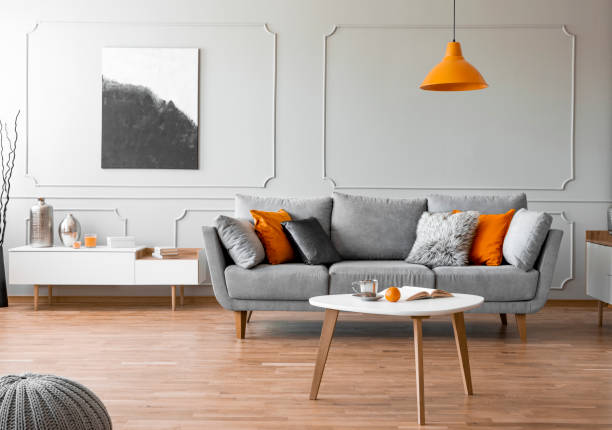 Orange lamp above wooden table in front of grey sofa in living room interior with poster. Real photo stock photo