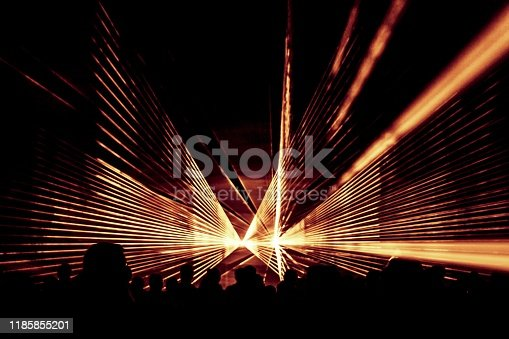 Luxury entertainment with audience silhouettes in nightclub event, festival or New Year's Eve. Beams and rays shining colorful lights.