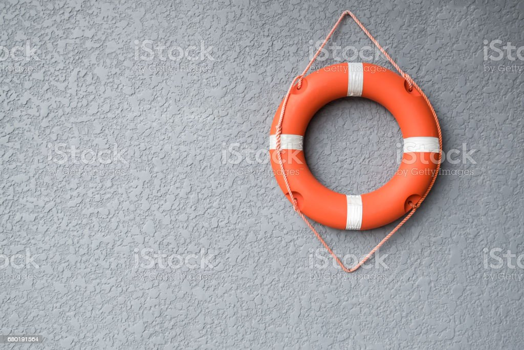 Orange life buoy hang on the grey wall stock photo