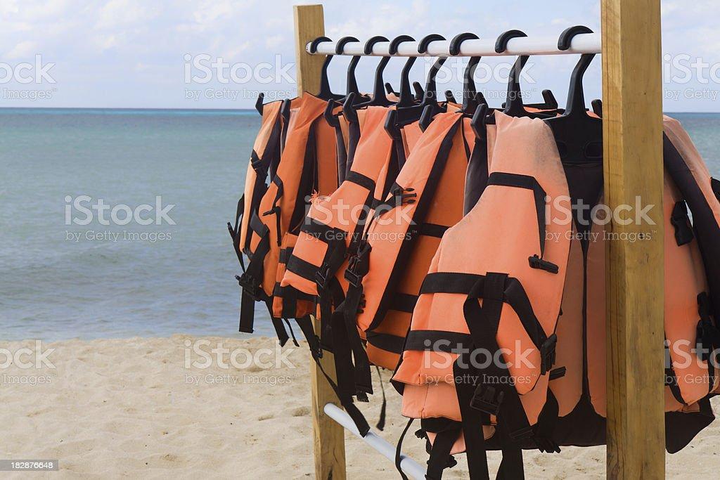 Orange Life Jackets Hnging on a Beach royalty-free stock photo