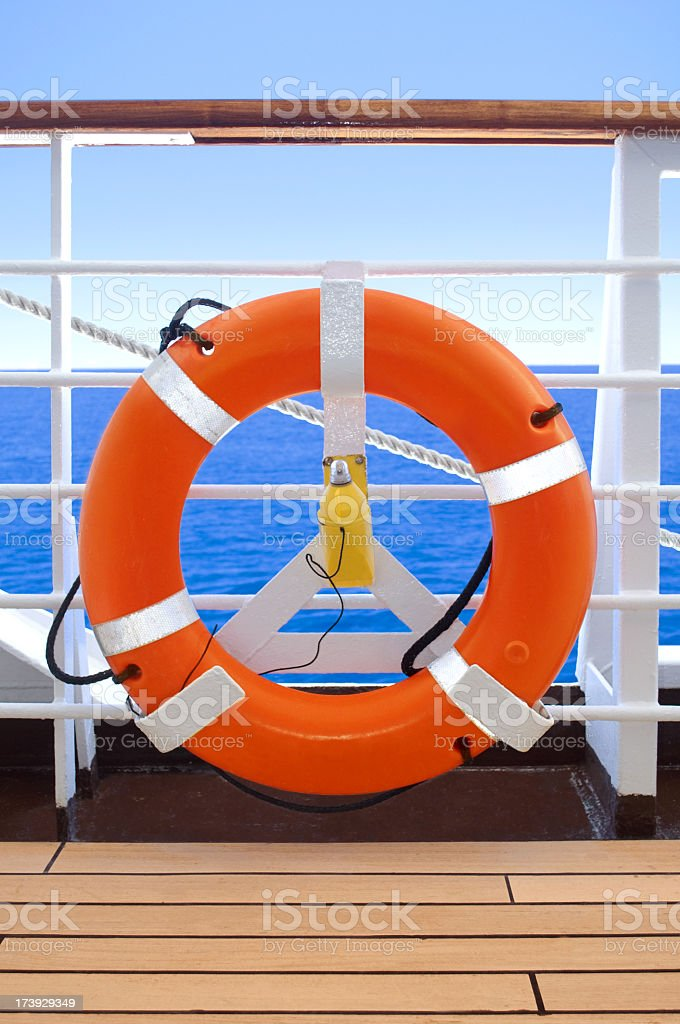 Orange life preserver on deck of cruise ship at sea royalty-free stock photo