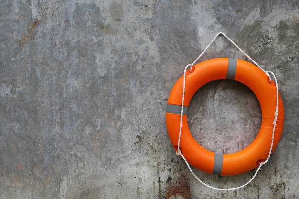 Orange Lifebuoy hanging on abstract cement wall Background. - foto stock
