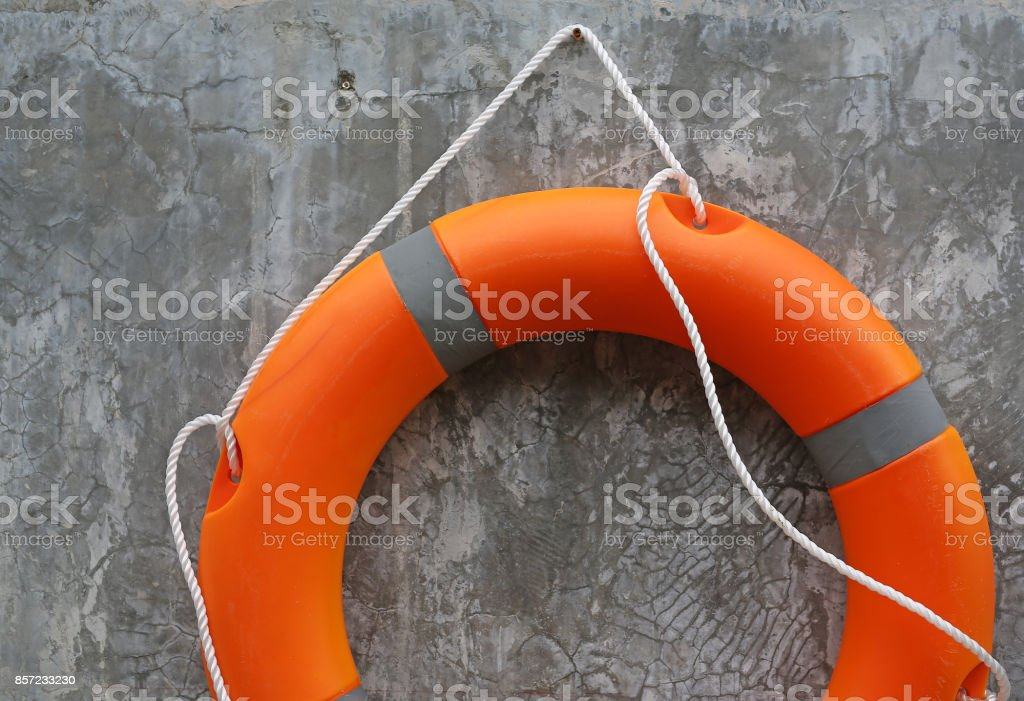 Orange Lifebuoy hanging on abstract cement wall Background. stock photo