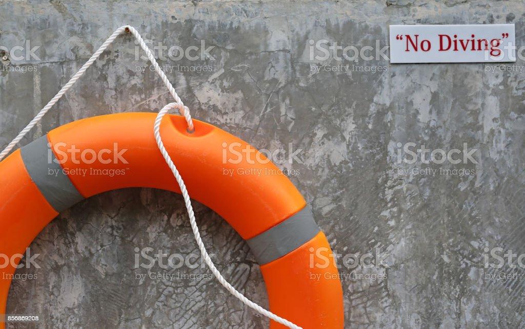 Orange Lifebuoy on a Gray Wall Background. stock photo