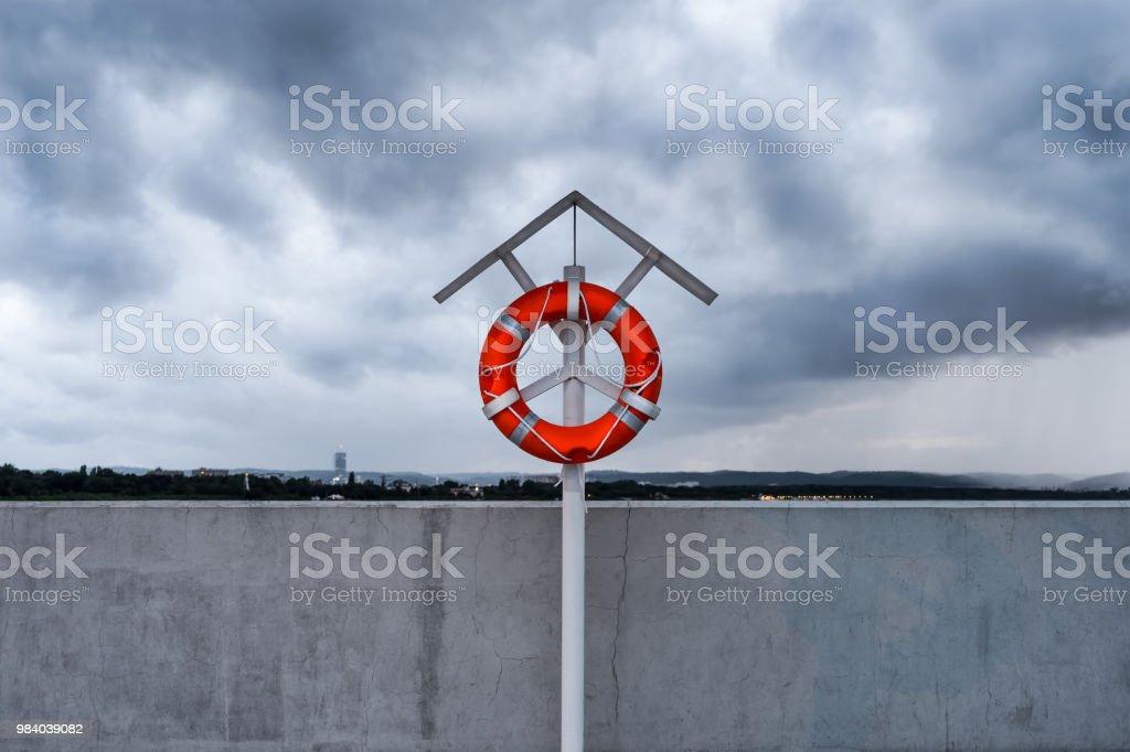 Orange lifebuoy on a stand on harbor pier. stock photo