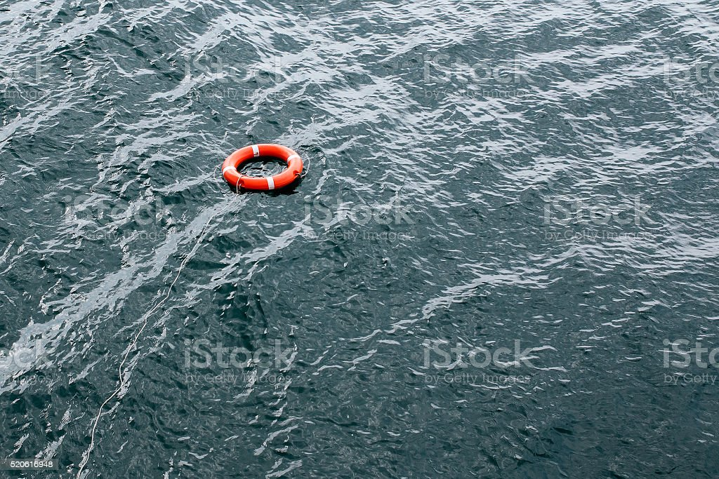 orange lifebuoy thrown to assist floats on water stock photo