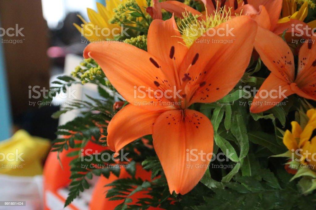 Oranje lelie in een bloemboeket met ook Carthamus en andere foto