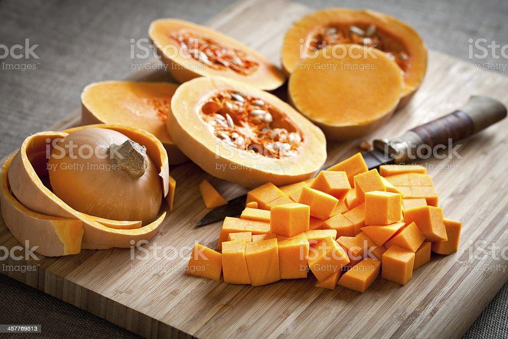 Orange long pumpkin cut into pieces stock photo