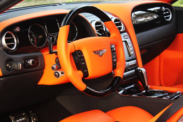 Orange luxury car Bentley Continental GT Mansory in the forest stock photo