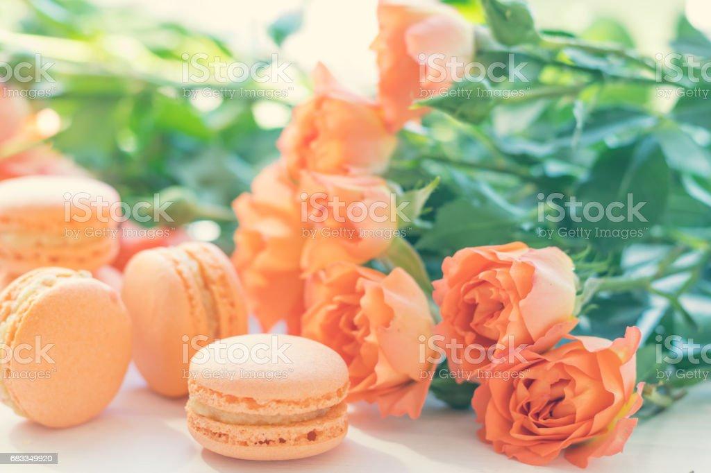 Orange macaroons and fresh little roses royalty-free stock photo
