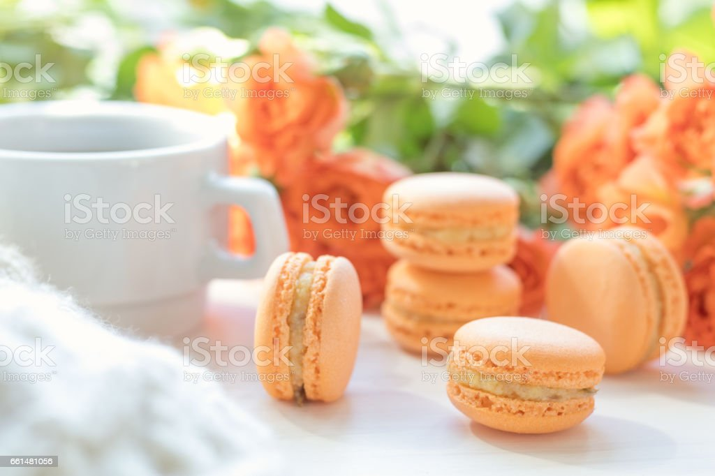Orange macaroons, cup of coffee and fresh roses royalty-free stock photo