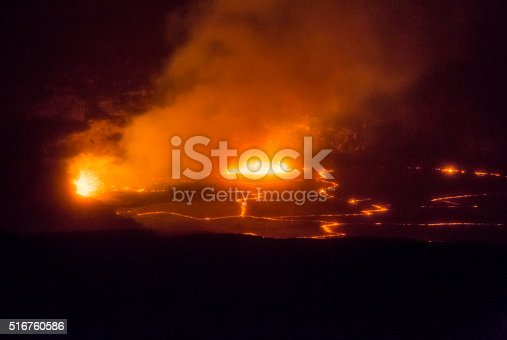Orange molten magma erupts at night inside Hawaii Island's Kilauea volcano. The Lava lake is glowing orange inside a volcanic caldera. A cloud of volcanic gasses is illuminated by glowing molten lava splattering into the air. The night image is horizontal and mostly dark except for the glowing areas.