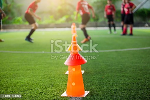 orange marker cones on green artificial turf for soccer training. Soccer equipment with blurry soccer team training in soccer academy.