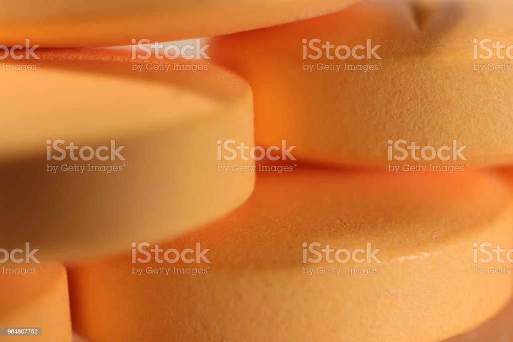 Orange Medicine Tablets Stacked on Top of Each Other. Pharmacy Pills Background. Macro Closeup. royalty-free stock photo