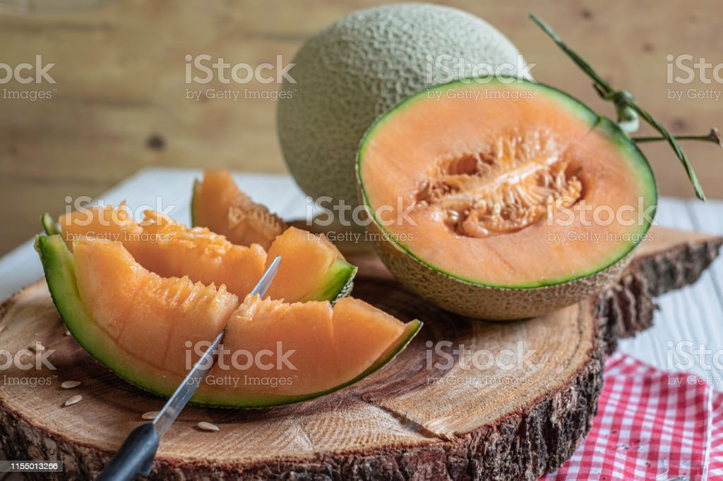 Orange Melon On Wooden Cutting Board And Table Stock Photo