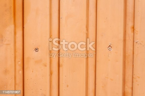 istock Orange metal fence with vertical corrugated stripes 1143701907