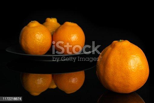 istock Orange minneola tangelo isolated on black glass 1172218574