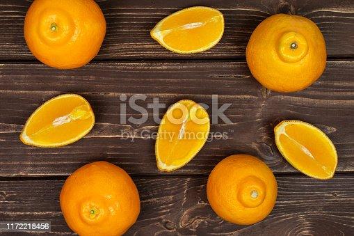 istock Orange minneola tangelo on brown wood 1172218456