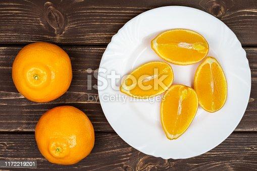 istock Orange minneola tangelo on brown wood 1172219201