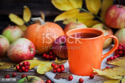 istock Orange mug on autumn background 614987756