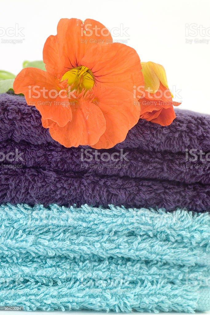 Orange nastursium Blume auf Haufen von blue Handtücher Lizenzfreies stock-foto