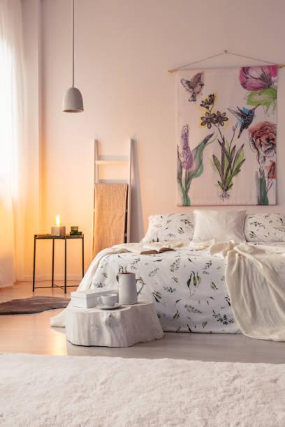 orange lampe licht in einem ferienhaus schlafzimmer interieur mit einem wandkunst über ein bett hängen. echtes foto. - cottage schlafzimmer stock-fotos und bilder