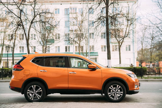 Orange Nissan X-Trail third generation Car Parked At Street. Side View stock photo
