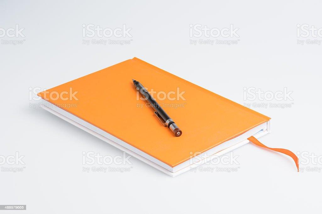 Orange note book and pen stock photo