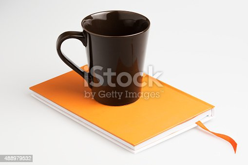 621843818istockphoto Orange note book white pen and cup 488979532