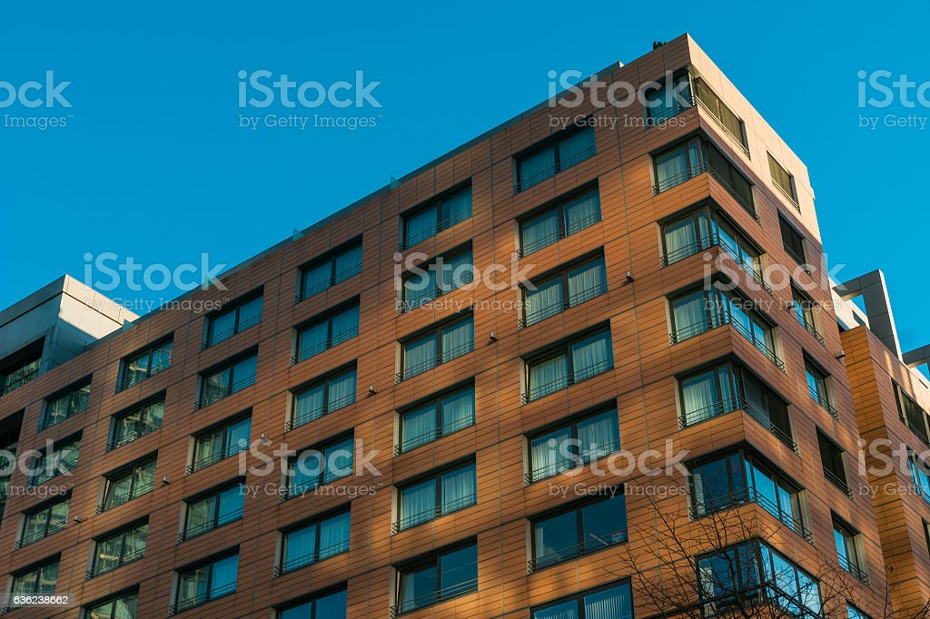 orange office building with light reflections and blue windows stock photo