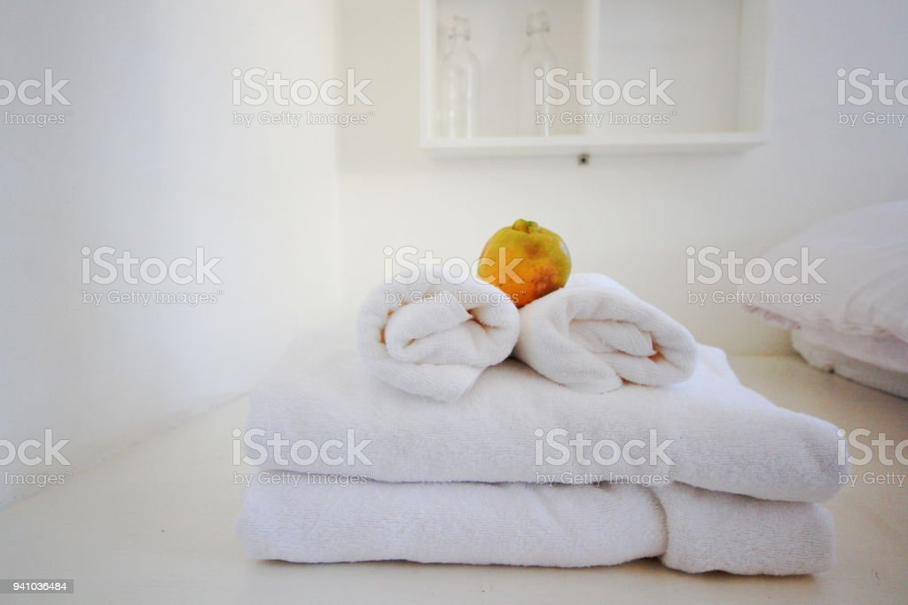 Orange on white pure towels on white bed. Interior of hotel bedroom. Comfort on White bed and pillow.wooden Furniture and design of vintage style stock photo