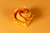 Orange origami rose on orange background. Japanese art of paper folding. Flat square sheet of paper transferred into a finished sculpture through folding and sculpting. Close up. Macro photo.
